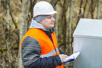 Engineer with documentation near electric enclosure