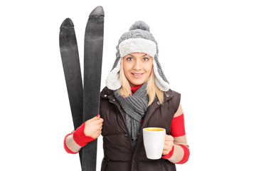 Woman holding a pair of skis and drinking hot tea