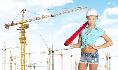 Woman in hard hat with large builders level on her shoulder