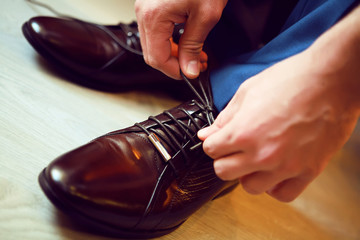 man tying shoes. wedding charges