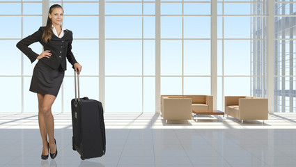 Businesswoman with travel bag in vast interior