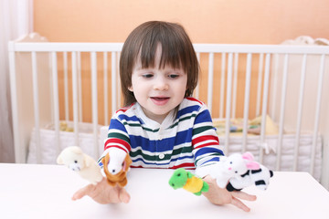 Lovely little boy (2.5 years) plays with finger puppets at home