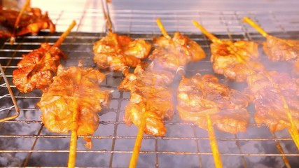 Close up frying pieces of meat in the grill on wooden sticks