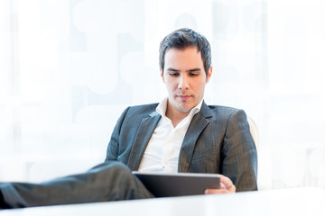 Serious young businessman reading his tablet-pc
