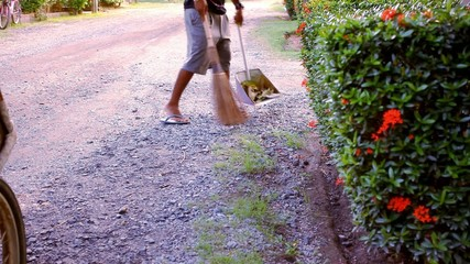 Janitor with broom sweeping fallen leaves. Video