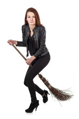 Young girl in black leather jacket riding wicked broom isolated