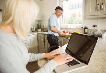 Happy mature blonde using laptop talking with husband