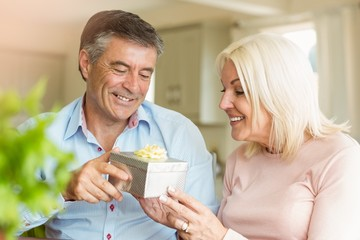 Happy mature man offering wife a gift