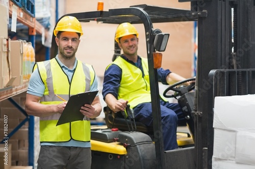 Smiling warehouse worker and forklift driver - 78824107