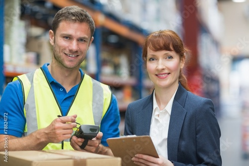 canvas print picture Worker and manager scanning package in warehouse