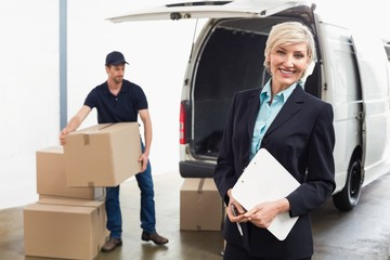 Delivery driver packing his van with manager smiling