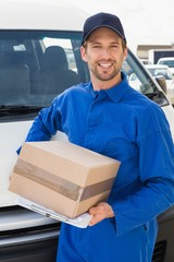 Delivery driver smiling at camera by his van holding parcel