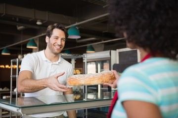 Waitress behind the counter giving loaf to customer