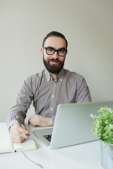 Smiling man with beard in glasses taking notes with laptop notep