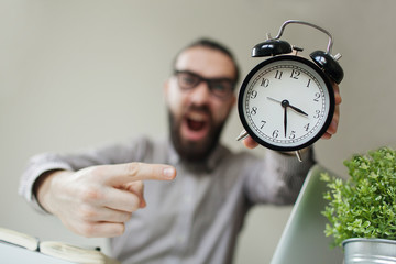 Angry boss with beard holds alarm clock screaming on camera