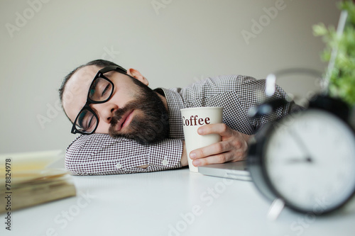 Man sleeps in office on table over laptop with coffee in hand - 78824978