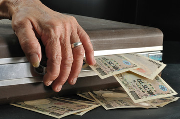 wrinkle senior hand touch suitcase full of Yen cash in dark room