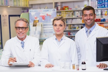 Team of pharmacists smiling at camera