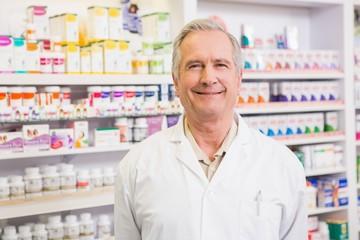 Smiling senior pharmacist standing