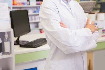 Mid section of junior pharmacist with arms crossed