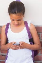 Cute pupil using mobile phone