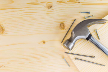 Hammer and nails on a wooden background