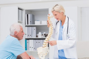 Female doctor explaining anatomical spine to senior man