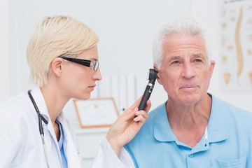 Doctor examining male patients ear with otoscope