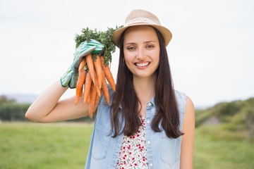 Happy brunette holding organic carrots