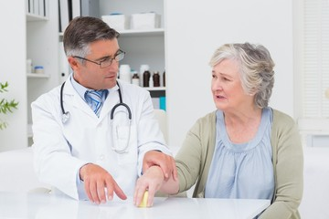 Doctor assisting patient to hold weight at table