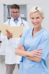 Nurse standing arms crossed while doctor reading reports