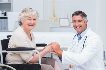 Happy doctor holding senior patients hands