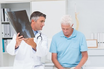 Doctor explaining x-ray while looking at sad senior patient