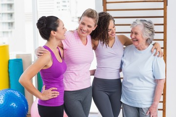 Female friends standing arms around in gym