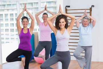 Friends practicing tree pose in fitness studio