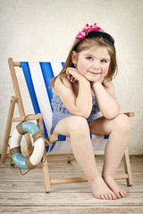 Little girl sitting on the sunbed wearing swimsuit