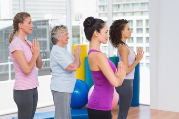 Female friends with hands clasped standing in gym