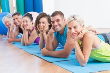 People relaxing on exercise mats at fitness studio