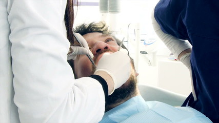 Closeup of man being checked by dentist
