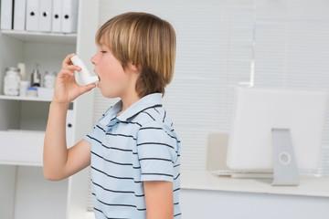 A little boy using inhaler