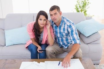 Portrait of worried couple calculating home finances