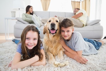 Siblings lying with dog while parents resting  on sofa