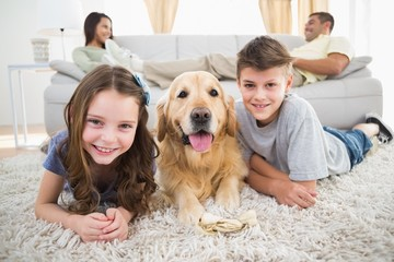 Siblings lying with dog while parents relaxing on sofa