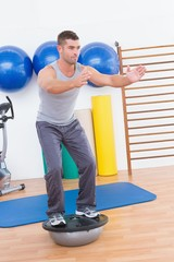 Concentrate man training in bosu ball