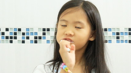 Little Asian child brushing her teeth