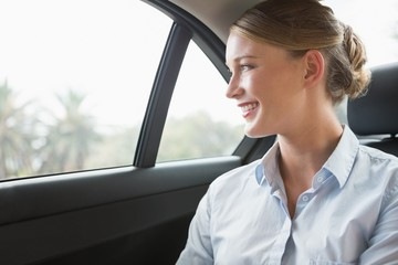 Smiling young businesswoman sitting in her car