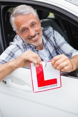 Driver smiling and tearing l plate