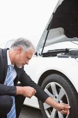 Businessman checking tire