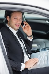 Businessman working in the drivers seat