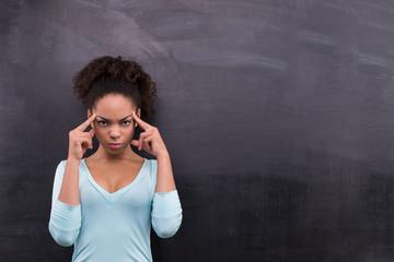 Thoughtful afro-american woman standing near chalkboard